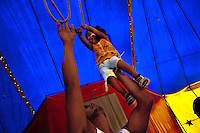 A little Colombian girl does a trapeze training with help of his father at the Circo Anny, a family run circus wandering the Amazon region of Ecuador, 4 July 2010. The Circo Anny circus belongs to the old-fashioned traveling circuses with a usual mixture of acrobat, clown and comic acts. Due to the general loss of popularity caused by modern forms of entertainment such as movies, TV shows or internet, these small family enterprises balance on the edge of survival. Circuses were pushed away and now they have to set up their shows in more remote villages. The circus art and culture is slowly dying.