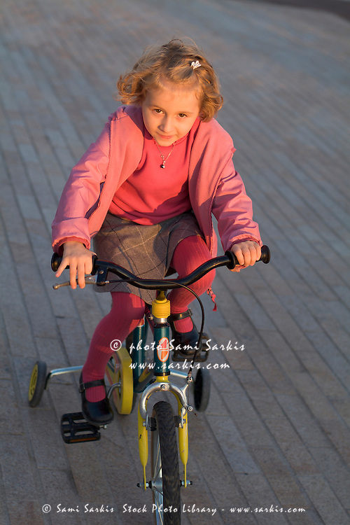 Blonde girl looking determined as she cycles along on her tricycle.