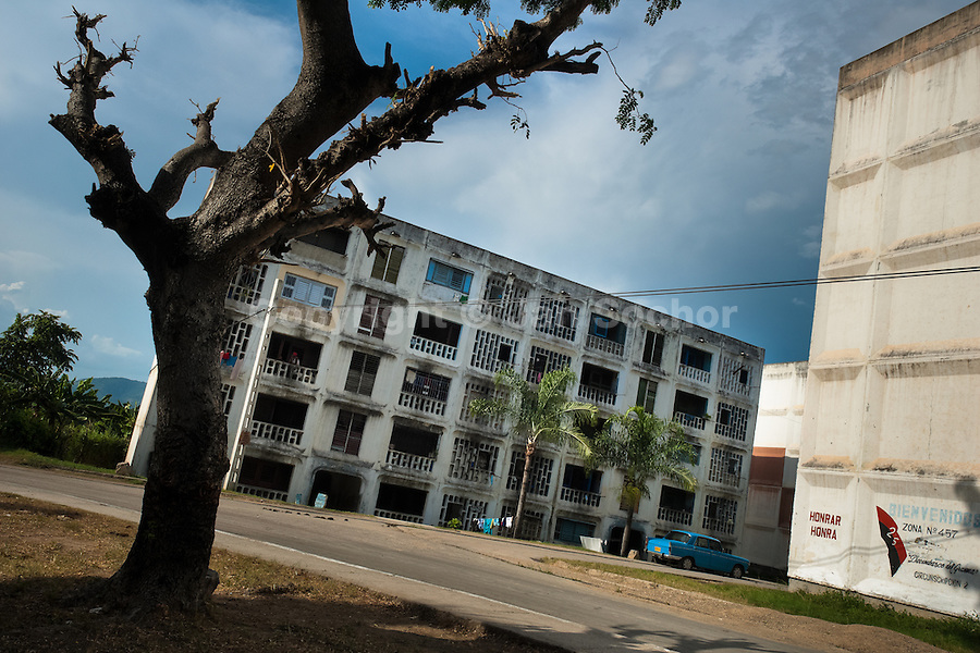 """A bare tree is seen in front of the apartment blocks in Abel Santamaría, a public housing periphery of Santiago de Cuba, Cuba, 31 July 2008. The Cuban economic transformation (after the revolution in 1959) has changed the housing status in Cuba from a consumer commodity into a social right. In 1970s, to overcome the serious housing shortage, the Cuban state took over the Soviet Union concept of social housing. Using prefabricated panel factories, donated to Cuba by Soviets, huge public housing complexes have risen in the outskirts of Cuban towns. Although these mass housing settlements provided habitation to many families, they often lack infrastructure, culture, shops, services and well-maintained public spaces. Many local residents have no feeling of belonging and inspite of living on a tropical island, they claim to be """"living in Siberia""""."""
