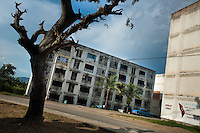 "A bare tree is seen in front of the apartment blocks in Abel Santamaría, a public housing periphery of Santiago de Cuba, Cuba, 31 July 2008. The Cuban economic transformation (after the revolution in 1959) has changed the housing status in Cuba from a consumer commodity into a social right. In 1970s, to overcome the serious housing shortage, the Cuban state took over the Soviet Union concept of social housing. Using prefabricated panel factories, donated to Cuba by Soviets, huge public housing complexes have risen in the outskirts of Cuban towns. Although these mass housing settlements provided habitation to many families, they often lack infrastructure, culture, shops, services and well-maintained public spaces. Many local residents have no feeling of belonging and inspite of living on a tropical island, they claim to be ""living in Siberia""."