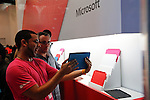 A worker shows the new Microsoft tablet Surface to a customer during the opening of Microsoft's store at Times Square in New York, October 25, 2012. . Photo by Kena Betancur / VIEW.
