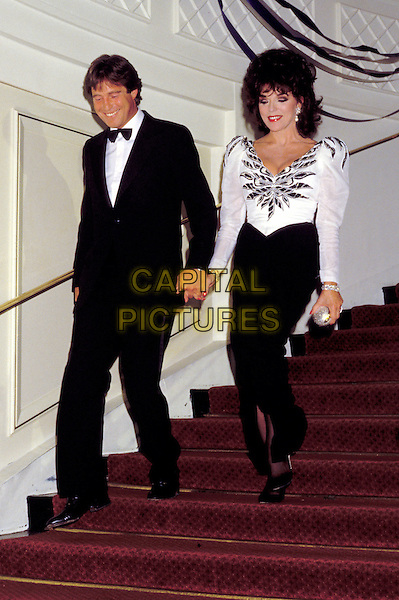 JOAN COLLINS & BILL WIGGINS.black and white dress, shoulder pads.Ref: 026.www.capitalpictures.com.sales@capitalpictures.com.© Capital Pictures