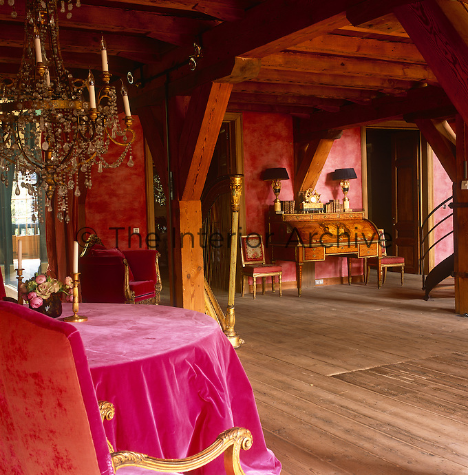 A country reception room with a heavily beamed ceiling and red walls. An antique bureau and two period chairs stand against one wall and a table is draped in a magenta pink cloth.