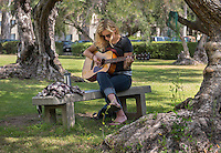 Student plays guitar under olive trees, near Booth Hall, April 3, 2013. (Photo by Marc Campos, Occidental College Photographer)