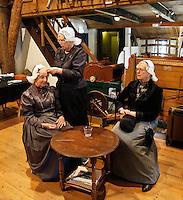 Westfriese Folkloredagen in Schagen . Sinds 1953 organiseert de Stichting ter Bevordering van de West-Friese Folklore de 10 West-Friese donderdagen. Deze donderdagen staan in het teken van o.a. leven, werken en kleden anno 1910.  Boerderij en Rijtuigmuseum Vreeburg. Vrouwen zetten hun kap op.