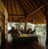 A suede double daybed and a group of comfortable chairs have been arranged on the private veranda outside the main bedroom