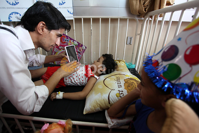 A wounded Palestinian child, plays at Al-Shifa hospital in Gaza city, on August 10, 2014. where he is receiving treatment for Injuries caused by Israeli shelling on neighborhoods in Gaza Strip. Photo by Ashraf Amra