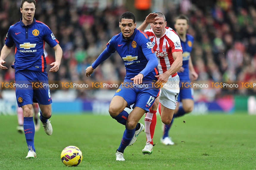 Chris Smalling of Manchester United battles for the ball with Jonathan Walters of Stoke City - Stoke City vs Manchester United - Barclays Premier League Football at the Britannia Stadium, Stoke-on-Trent - 01/01/15 - MANDATORY CREDIT: Greig Bertram/TGSPHOTO - Self billing applies where appropriate - contact@tgsphoto.co.uk - NO UNPAID USE