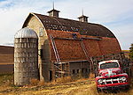 Two men with scaffolding and ladders put a new roof on an old barn in the Palouse region of WA. An old red truck and silo complete the pictorial farm scene.