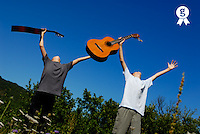 Two boys (11-13) standing in meadow, holding guitars in outstretched arms, low angle view (Licence this image exclusively with Getty: http://www.gettyimages.com/detail/sb10065474be-001 )