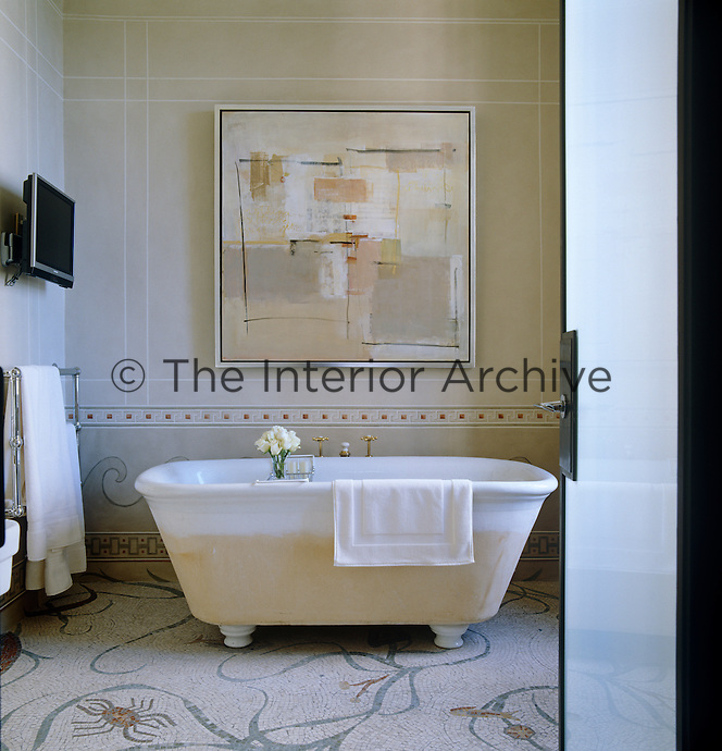 A bathroom is decorated in tones to complement a large abstract painting displayed above the free-standing bath