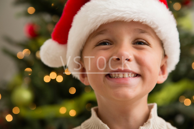 Smiling boy (6-7) wearing Santa hat