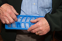 Man age 63 removing ice cubes from tray. St Paul Minnesota USA