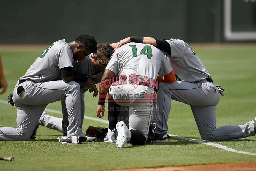 Members of the Augusta GreenJackets take a moment of reflection before a game against the Greenville Drive on Thursday, May 17, 2018, at Fluor Field at the West End in Greenville, South Carolina. Augusta won, 2-1. (Tom Priddy/Four Seam Images)