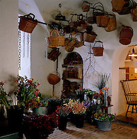 A collection of wicker baskets hangs from the ceiling above buckets of flowers in a corner of the flower room