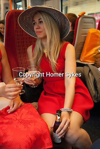 Two young women, drinking champagne from plastic cups on train journey to Royal Ascot.