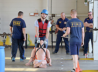 NWA Democrat-Gazette/BEN GOFF &bull; @NWABENGOFF<br /> Zack Hutcheson of Elkins, currently with the Elkins Volunteer Fire Department, drags a mannequin on Saturday Aug. 15, 2015 at Springdale Fire Department station No. 1 as he and other prospective firefighters take the Candidate Physical Ability Test. Candidates have 10 min, 20 sec. to complete a course with eight events, all while wearing a 50 lbs. weight vest. Candidates have three opportunities over several weeks to pass the test, earning certification that will be recognized by participating departments around the country as part of the application process for firefighting positions.