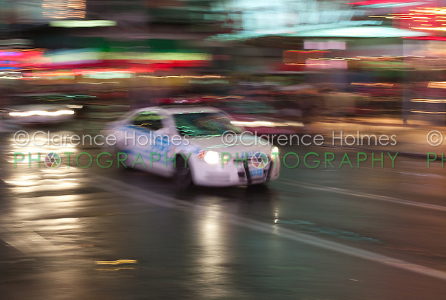 Motion blurred abstraction of police car rushing through Times Square