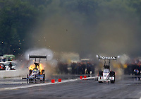 Aug 17, 2014; Brainerd, MN, USA; NHRA top fuel dragster driver Larry Dixon (left) blows his engine while racing alongside Antron Brown during the Lucas Oil Nationals at Brainerd International Raceway. Mandatory Credit: Mark J. Rebilas-