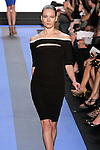 Teva walks runway in a carbon black jersey ¾ sleeve off the shoulder draped cocktail dress with white leather trim, by Monique Lhuillier, from the Monique Lhuillier Spring 2012 collection fashion show, during Mercedes-Benz Fashion Week Spring 2012.