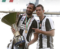 Calcio, Serie A: Juventus vs Crotone. Torino, Juventus Stadium, 21 maggio 2017.<br /> Juventus&rsquo; Giorgio Chiellini, left, and Stephan Lichsteiner hold the trophy during the celebrations for the victory of the sixth consecutive Scudetto at the end of the Italian Serie A football match between Juventus and Crotone at Turin's Juventus Stadium, 21 May 2017. Juventus defeated Crotone 3-0.<br /> UPDATE IMAGES PRESS/Isabella Bonotto