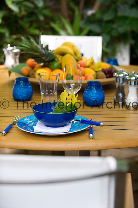 An exotic yellow flower wrapped in a banana leaf has been placed in each place setting
