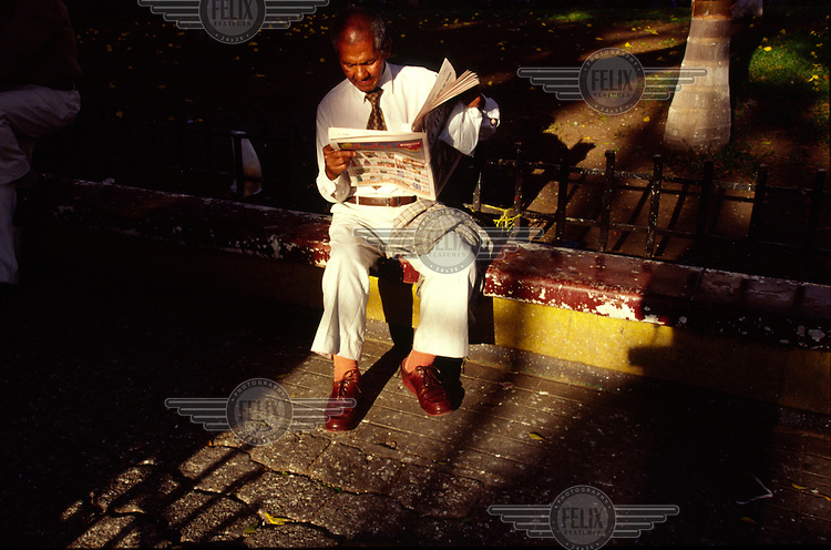 A man reads a newspaper in a park in the afternoon sun.