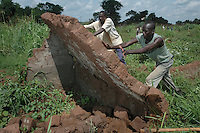 Workers demolish abandoned mud-brick-walled huts in Ogur camp in the Lira district in Northern Uganda. Left standing the huts become a favorite for local thugs to use in victimizing locals. The United Nations High Commission on Refugees (UNHCR) has begun a program to demolish the abandoned huts. As many as two million people were forced to leave their homes in northern Ugandan districts to escape the violence of the Lord's Resistance Army. In September of 2006, the LRA and Ugandan government have  observed a ceasefire while engaged in peace talks to end the conflict. As a result many residents of camps for the internally displaced have been slowly returning to their villlages to begin again.  (Rick D'Elia)