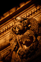 Detail of a putto, 18th century, by Ignazio Marabitti, with a pigeon perched on its head, on the facade of the Cathedral, or Duomo, Ortigia, Syracuse, Sicily, pictured on September 13, 2009, in the afternoon. The Duomo di Siracusa (Santa Maria delle Colonne) was originally built by Bishop Zosimo in the 7th century AD over the Greek Temple of Athena, 5th century BC, whose Doric columns still adorn the present facade, which was rebuilt in 1725-53 by Andrea Palma. The island Ortigia is the historic centre of Syracuse. Today the city is a UNESCO World Heritage Site. Picture by Manuel Cohen.