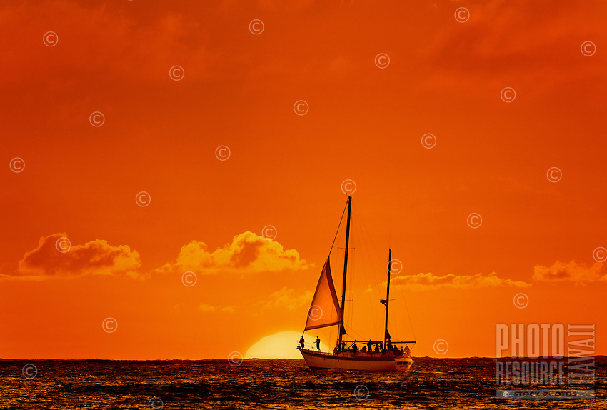 A group of friends on a sailboat waiting with anticipation for the green flash at sunset.