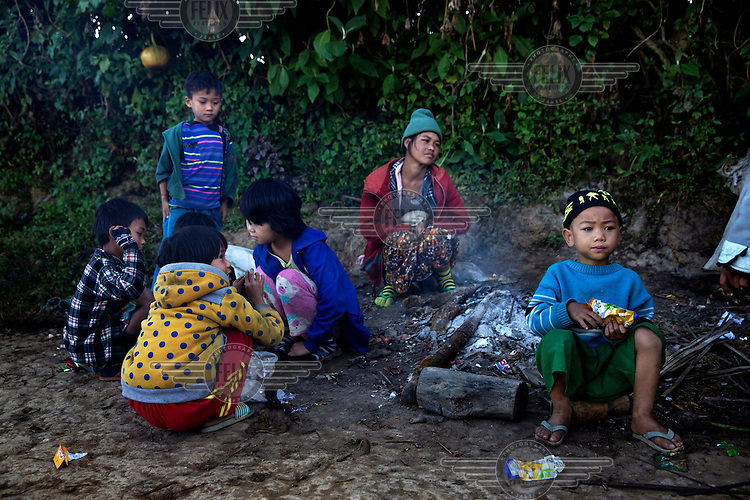 Children and an adult warm themselves by a fire in the early morning in Long Douay Village in a Shan State Army - South controlled area of Shan State.