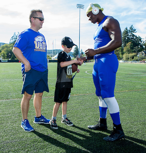 26 August 2016: Charles Nwoye (92) of the Thunderbirds meets a young fan and his father prior to the start of the   Vancouver Island Thunder Bowl.  Action during a men's CIS exhibition Football game between the University of British Columbia Thunderbirds and the visiting University of Manitoba Bisons at Westhills Stadium in Langford, BC, Canada. Final Score: Manitoba 50 UBC 7 ****(Photo by Bob Frid/UBC Athletics  2016 - All Rights Reserved****)