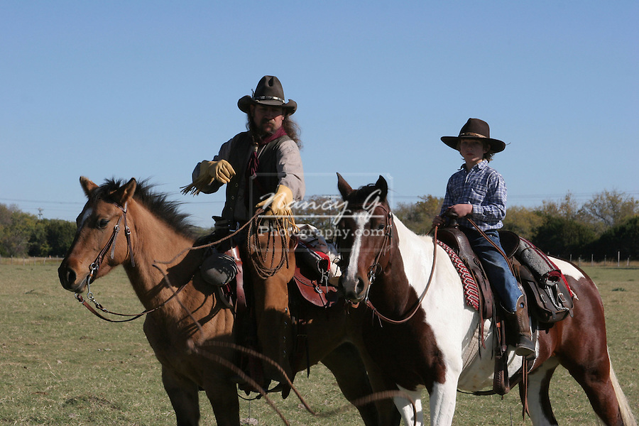 A cowboy father showing his son how to rope a cow on the ranch by throwing the rope