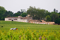 Chateau Figeac seen from the back with winery buildings, vineyard and a tractor Saint Emilion Bordeaux Gironde Aquitaine France