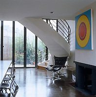 A circles painting by Carol Robertson hangs above the fireplace in this glass and concrete dining room