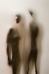 Partially silhouetted man & woman behind translucent fabric