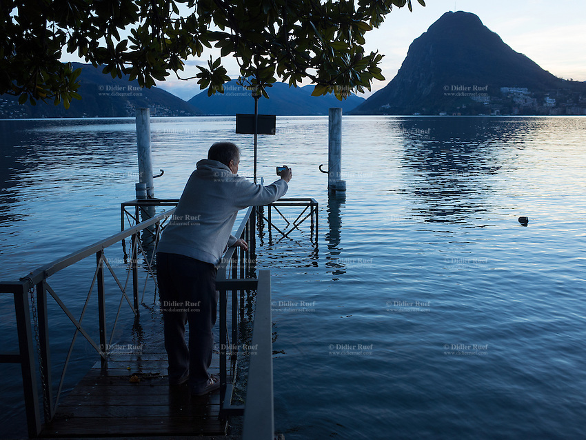 Switzerland. Canton Ticino. Lugano. Flooding on the lake. A tourist on a jetty takes pictures with a mobile phone. 26.11.14 © 2014 Didier Ruef