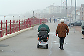 An elderly couple on the promenade in the Yorkshire seaside resort of Bridlington on Easter Bank Holiday.