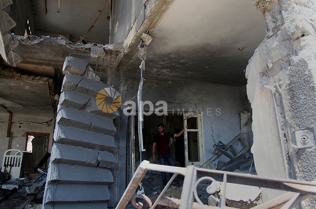 "Palestinians inspect a damaged house was hit by an Israeli military strike in Gaza City on August 10, 2014. A senior Hamas official said there was a ""weak"" possibility that Gaza truce talks would succeed and that Palestinian negotiators could leave Cairo after a meeting with Egyptian mediators. Photo by Ezz al-Zanoun"