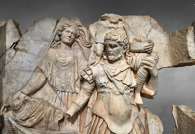 Close up of a Roman Sebasteion relief  sculpture of Aineas' flight from Troy, Aphrodisias Museum, Aphrodisias, Turkey.  Against a grey background.<br /> <br /> Aineas in armour carries his aged farther Anchises on his shoulders and leads his young son Lulus by his hand. They are fleeing from the sack of Troy. The figure floating behind is Aphrodite, Aineas' mother: she is helping their escape. Old Anchises carries a round box that held images of Troy's ancestral gods.