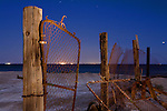 A rusted gate and fencing at a flooded neighborhood in Bombay Beach, California on the shore of the Salton Sea