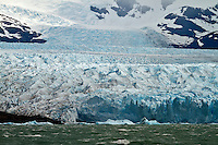 Glacier Perito Moreno stretches for km. into the distance in Parque Nacional los Glaviares, Argentina.  Note the hikers in the lower left of the glacier for scale.