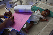 A doctor checks the report of a new born baby in the intensive care unit of the nursery  of the Duncan Hospital in Raxaul, Bihar, India.