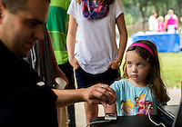 NWA Democrat-Gazette/JASON IVESTER <br /> Bella Vista Police Sgt. Clayton Roberts scans the fingerprints of Savanna (cq) Sexton, 4, of Bella Vista on Tuesday, Aug. 4, 2015, at Riordan Hall in Bella Vista. The police department hosted the Night Out event which featured free games and food for families.
