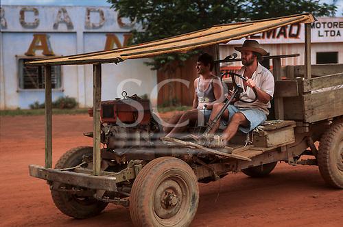Juruena, Mato Grosso State, Brazil. Settler driving a home-made truck on a red dirt road.