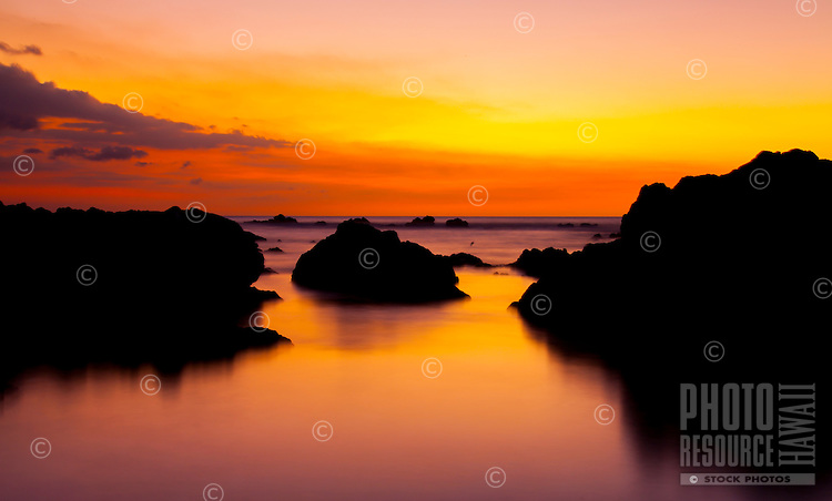 Red, orange, yellow and purple colors create a colorful sunset, with lava rocks reflected in tide pools, Puako, Big Island.