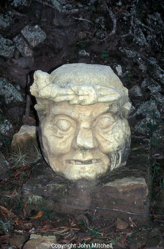 Toothless Old Man of Copan or Pauahtun head sculplture at the Maya ruins of Copan