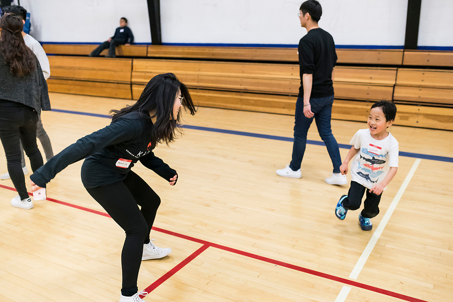 A volunteer from UW-Madison's Korean American Student Association (KASA) plays with children during a lunar new year event hosted by Families Through Korean Adoption (FTKA) in the gym and school cafeteria of St. Dennis Church in Madison, Wis., on Feb. 10, 2018. The event celebrated the passing of the lunar new year, and is one of several events for FTKA-member families and children to gather and enjoy cultural fun, food and play. (Photo by Jeff Miller - www.jeffmillerphotography.com)