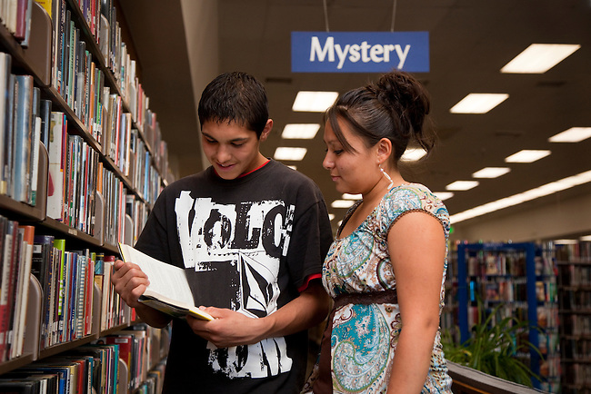 Two Native American teenagers share a book next to a book shelf while visiting a library.