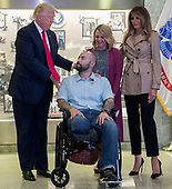 US President Donald J. Trump (L), with First Lady Melania Trump (R), talks with Sergeant First Class Alvaro Barrientos (2-L), with his wife Tammy Barrientos (2-R), after awarding the Purple Heart to him during a visit to Walter Reed National Military Medical Center in Bethesda, Maryland, USA, 22 April 2017. Sergeant First Class Alvaro Barrientos was recently injured in Afghanistan while deployed and for the wounds he sustained, he is receiving the Purple Heart.<br /> Credit: Shawn Thew / Pool via CNP
